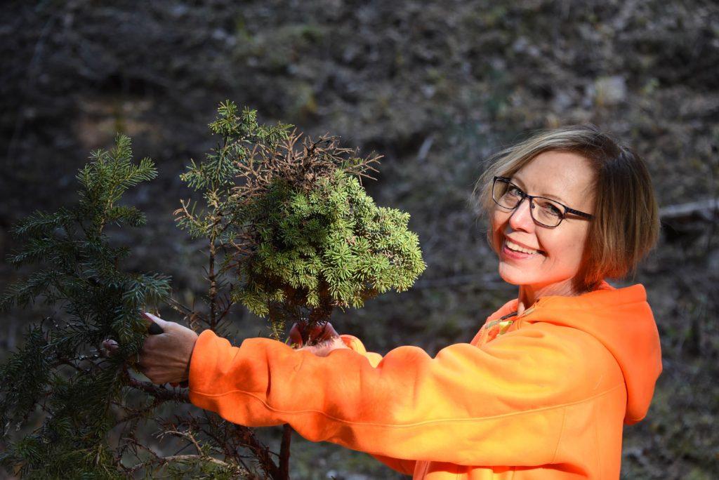 Cheryl holding tiny subalpine fir broom named 'Quark'
